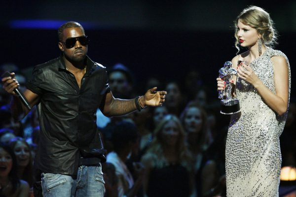 """FILE - In this Sept. 13, 2009 file photo, singer Kanye West takes the microphone from singer Taylor Swift as she accepts the """"Best Female Video"""" award during the MTV Video Music Awards in New York. (AP Photo/Jason DeCrow, file)"""
